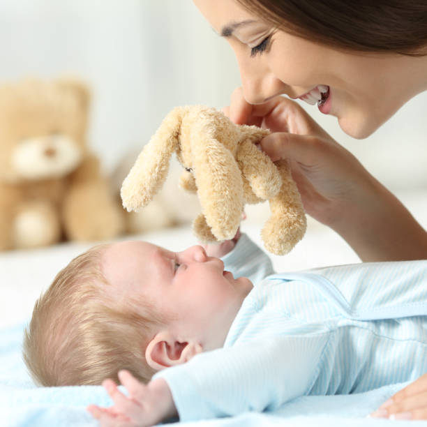 Mother playing with her baby with a teddy stock photo