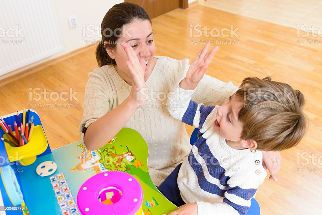 Mother playing with her child and encouraging him Mother playing with her child some creativity game and encouraging him A Helping Hand Stock Photo