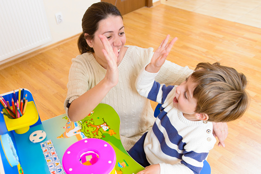 Mother Playing With Her Child And Encouraging Him Stock Photo - Download Image Now