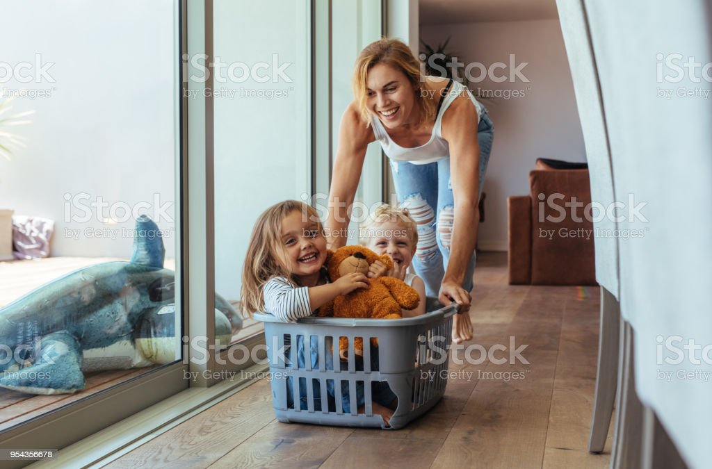 Mother playing with her children at home stock photo