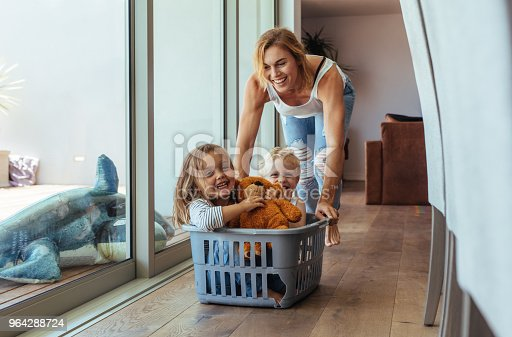 954356678 istock photo Mother playing with her children at home 964288724
