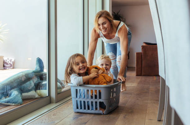Mother playing with her children at home Happy young mother pushing children sitting in laundry basket. Mother and children playing at home. laundry basket stock pictures, royalty-free photos & images