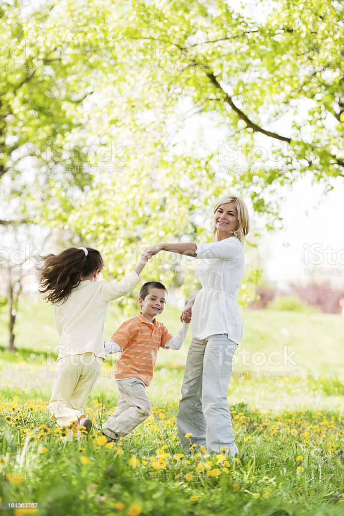 Mother playing with her children in a park royalty-free stock photo