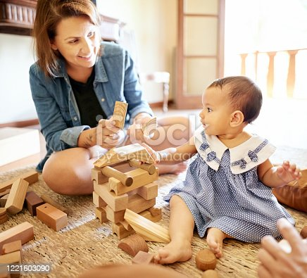 872316662 istock photo Mother playing with her daughter at home 1221603090