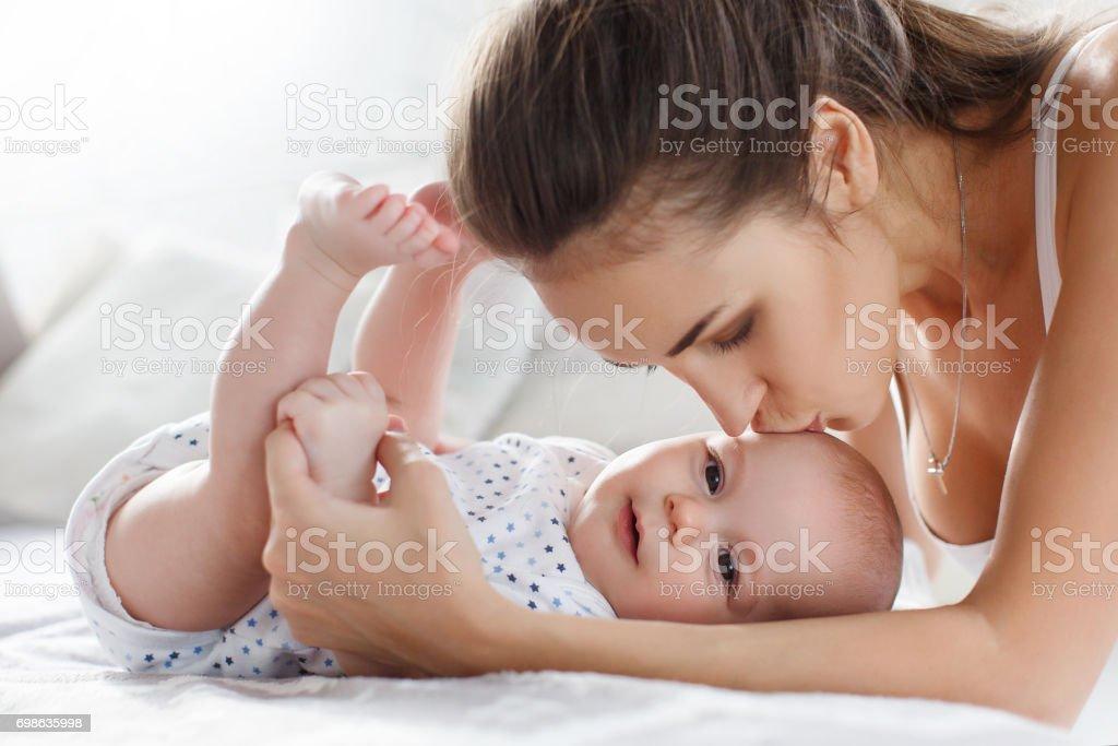 Mutter mit ihrem neugeborenen Sohn auf Bett liegend spielen – Foto