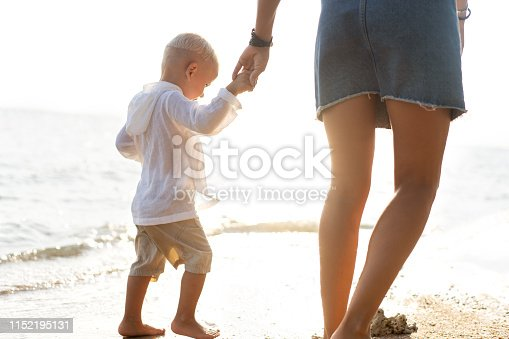 istock mother playing with her son at sunset on a tropical beach 1152195131