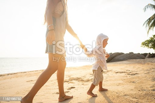 istock mother playing with her son at sunset on a tropical beach 1152195732