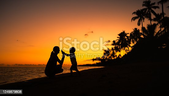Happy mother and child silhouette interacting playing on the beach.