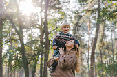 Young Caucasian mother playing with little son in forest in autumn