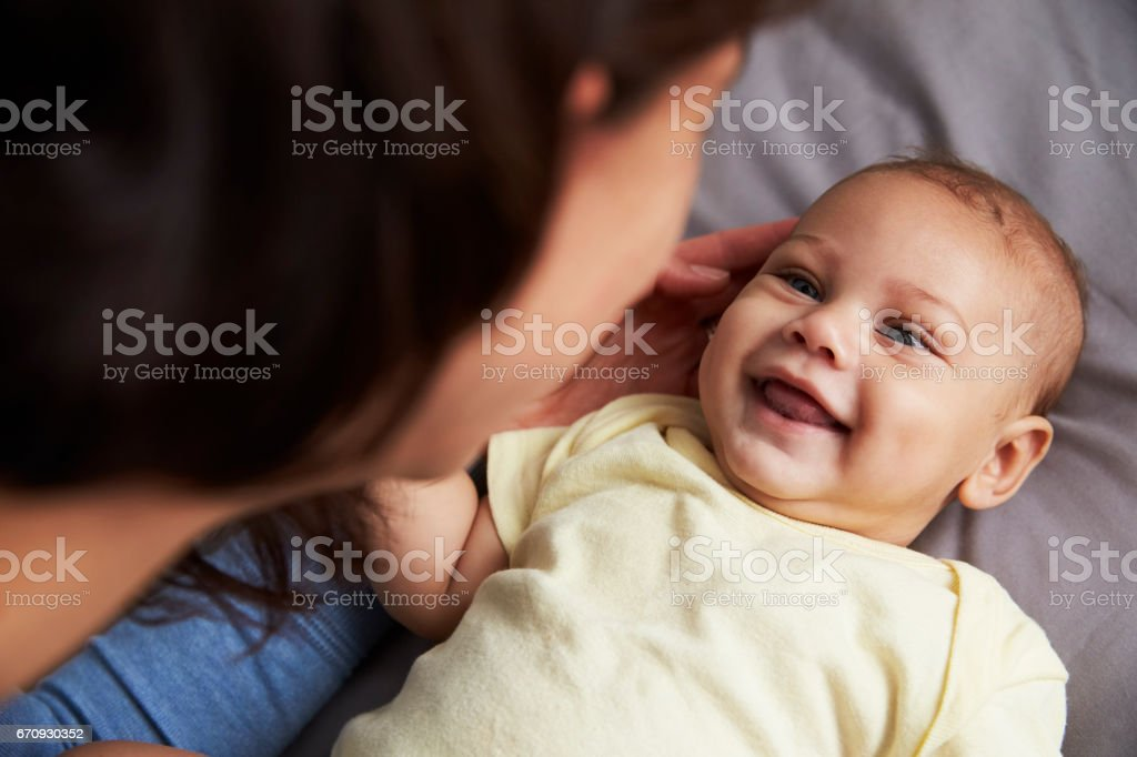 Mother Playing With Newborn Baby Son Lying On Bed In Nursery stock photo