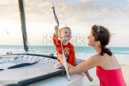 Mother Playing with Son on Boat at Beach Sunset