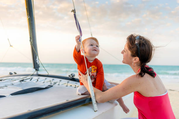 Mother Playing with Son on Boat at Beach Sunset stock photo