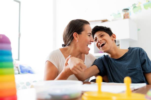 脳性麻痺の息子と一緒に遊んでいる母 - 障害者 ストックフォトと画像