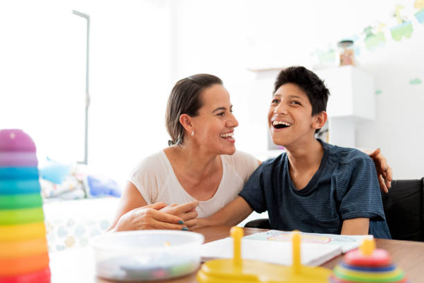Mother playing with son with Cerebral Palsy stock photo