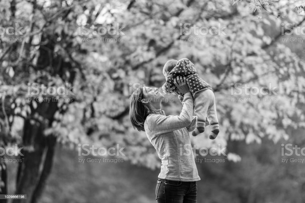 Mother playing with young baby girl outdoors stock photo