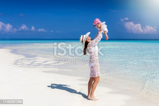 Attractive mother in white summer dress plays with her baby daughter on a tropical beach in the Maldives