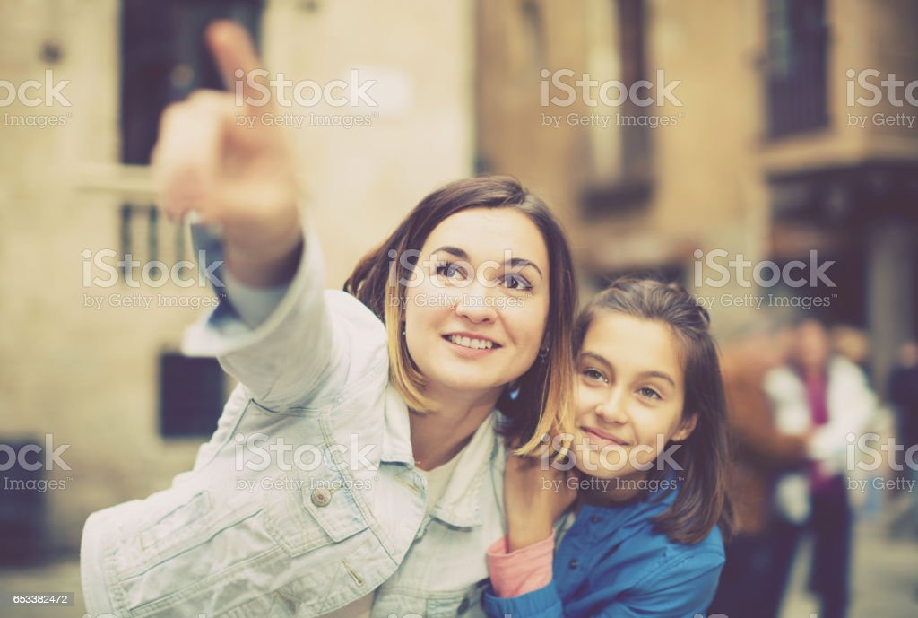 Mother pointing to daughter new sight stock photo