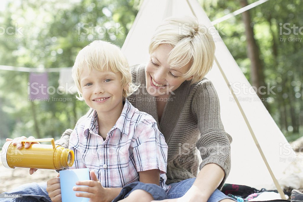Mother pouring drink from thermos for son royalty-free stock photo