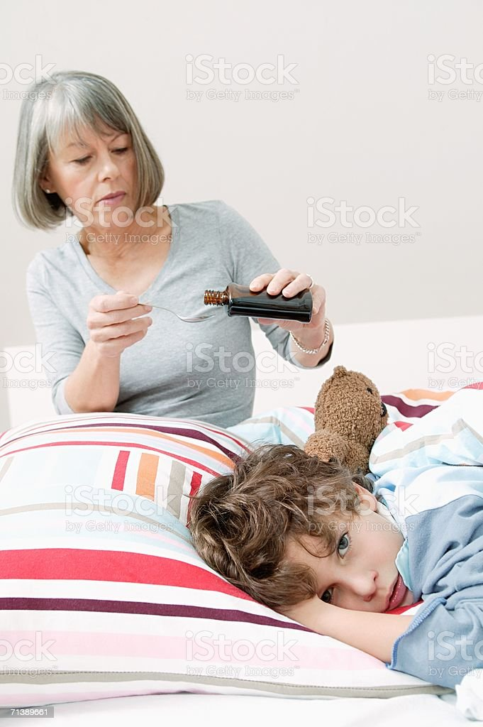 Mother pouring medicine for son royalty-free stock photo