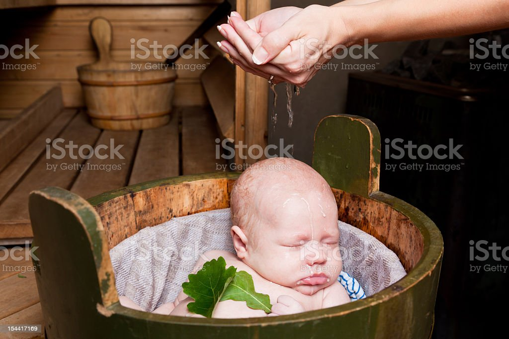 Mother Pouring Water On Baby Having Bath In Rural Sauna Stock Photo ...