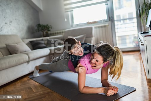 171274866 istock photo Mother practicing yoga with toddler boy at home 1216623269