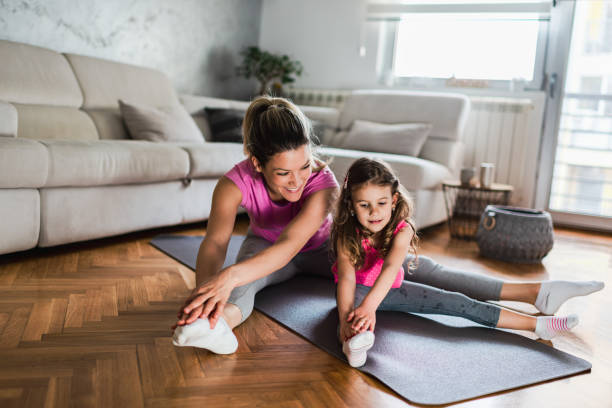 Mother practicing yoga with toddler daughter at home Shot of a young mother practicing yoga with toddler daughter at home. Illness prevention during COVID-19 isolation. flatten the curve stock pictures, royalty-free photos & images