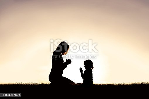 A silhouette of a Christian mother teaching her young child to pray as they sit peacefully outside, against the sunset in the sky.