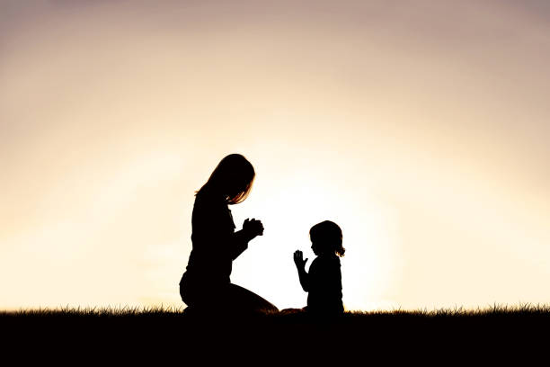 Mother Praying with her Young Child Outside at Sunset. stock photo