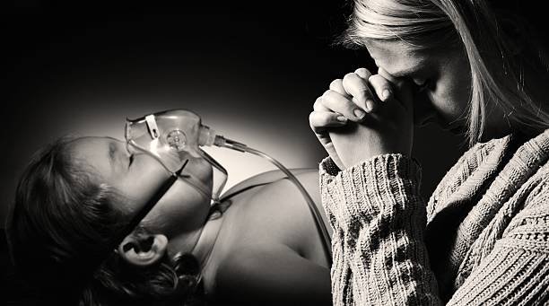 Mother prays for the health of seriously ill daughter. stock photo