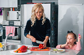 Mother preparing a salad on kitchen and child eats vegetables