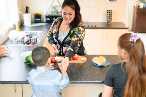 Mother preparing breakfast for kids. stock photo