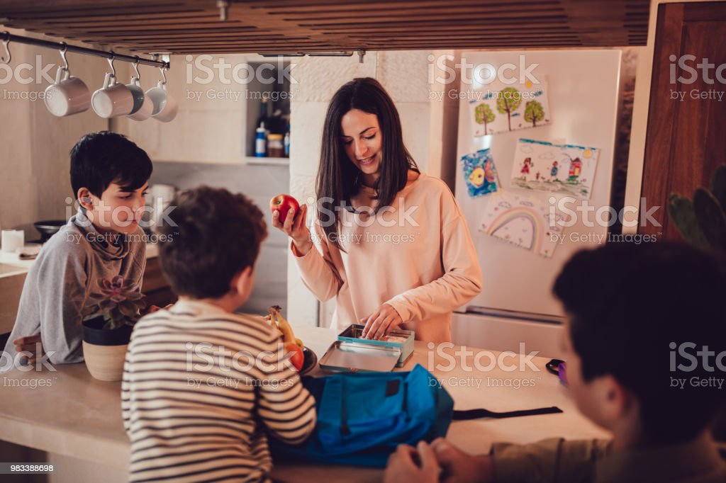 Mother preparing healthy food lunch boxes for children in kitchen Mother preparing lunch boxes with healthy food and snacks for sons before going to school 10-11 Years Stock Photo