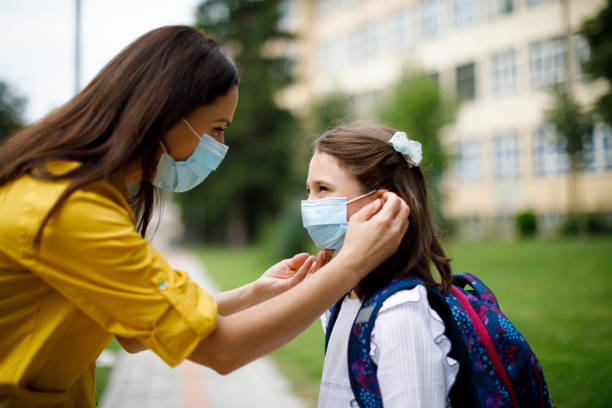 Mother preparing her child for school in front of the school stock photo