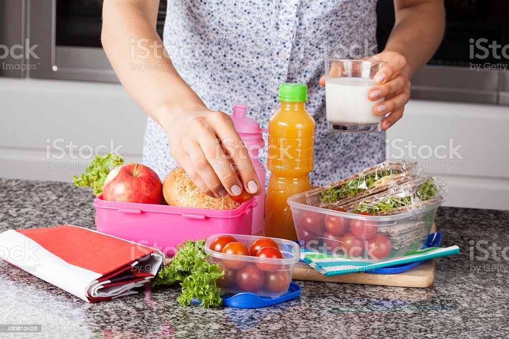 Mother preparing lunch box stock photo