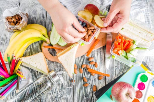 anne hazırlamak okul öğle yemeği kutu - atıştırmalıklar stok fotoğraflar ve resimler