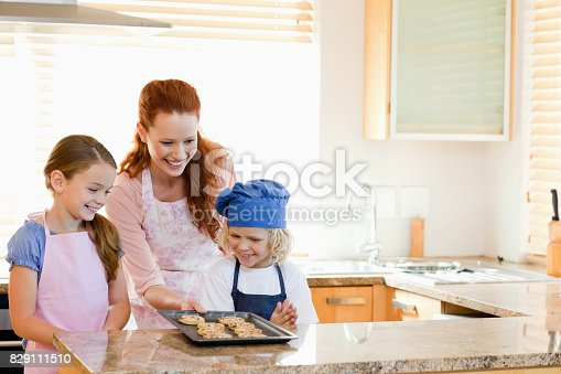 Smiling mother presenting finished cookies to her children