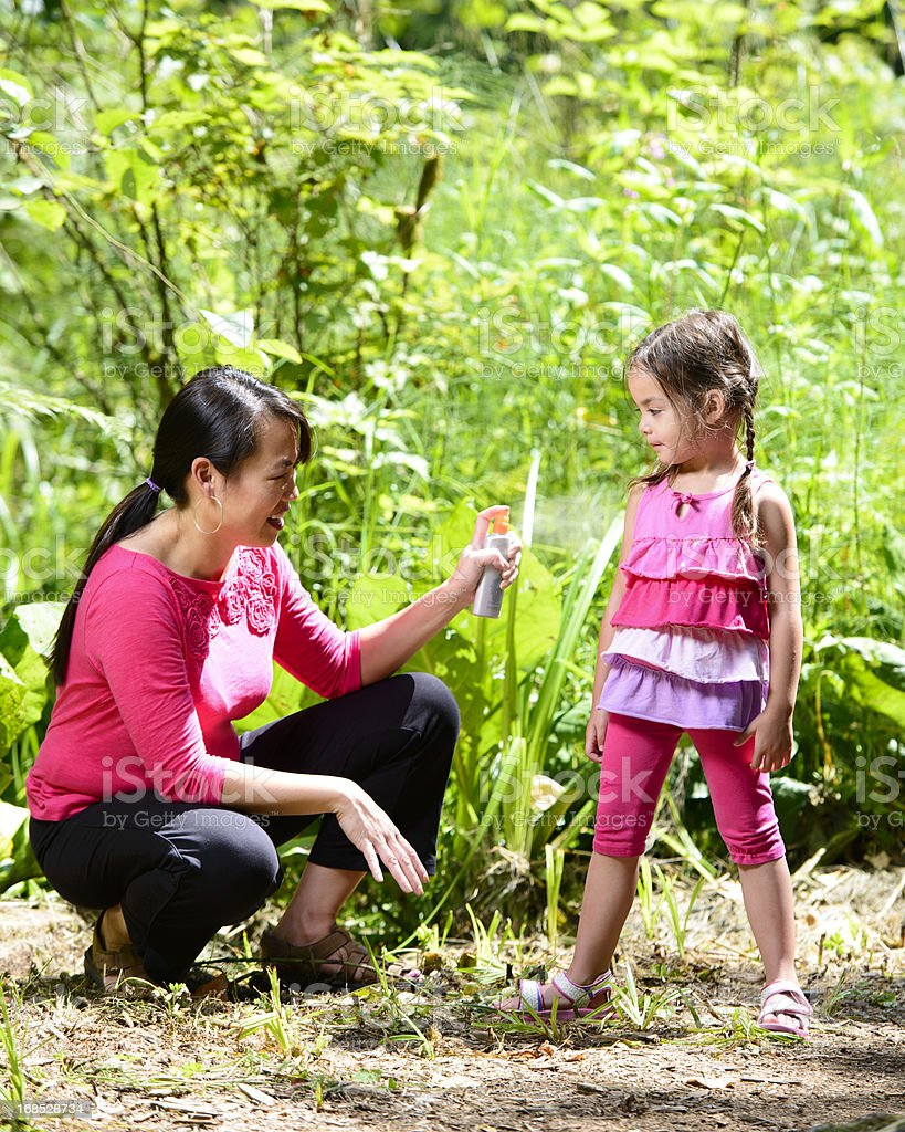 Mother protecting daughter by using bug spray stock photo