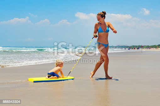 849648098 istock photo Mother pull baby son on surfing board by sea beach 888343304