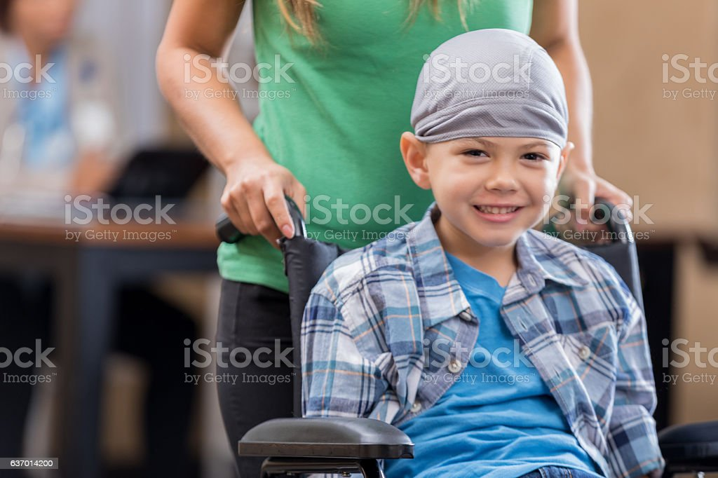 Mother pushes sick little boy in wheelchair stock photo