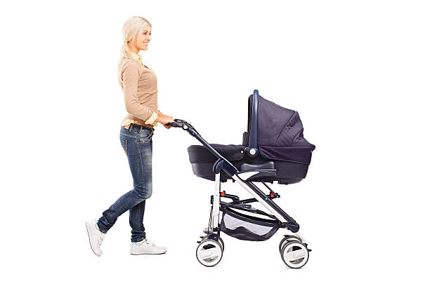 Mother pushing a baby stroller stock photo