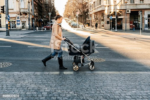 istock Mother pushing a stroller in the street 898802924