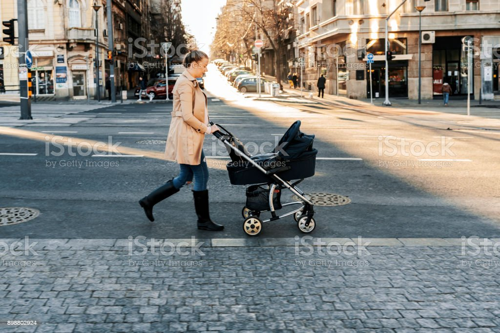 Mother pushing a stroller in the street stock photo