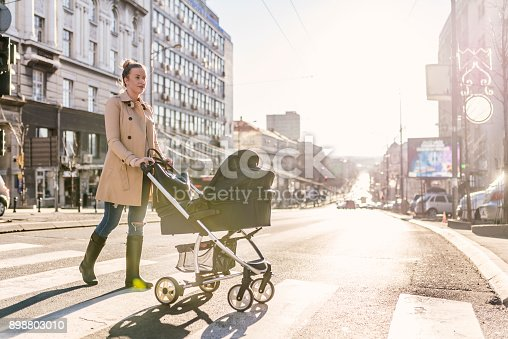 istock Mother pushing baby stroller on lined pedestrian crossing 898803010