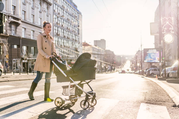 Mother pushing baby stroller on lined pedestrian crossing stock photo