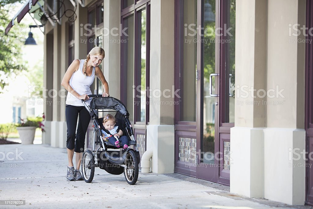 Mother pushing baby stroller on sidewalk royalty-free stock photo