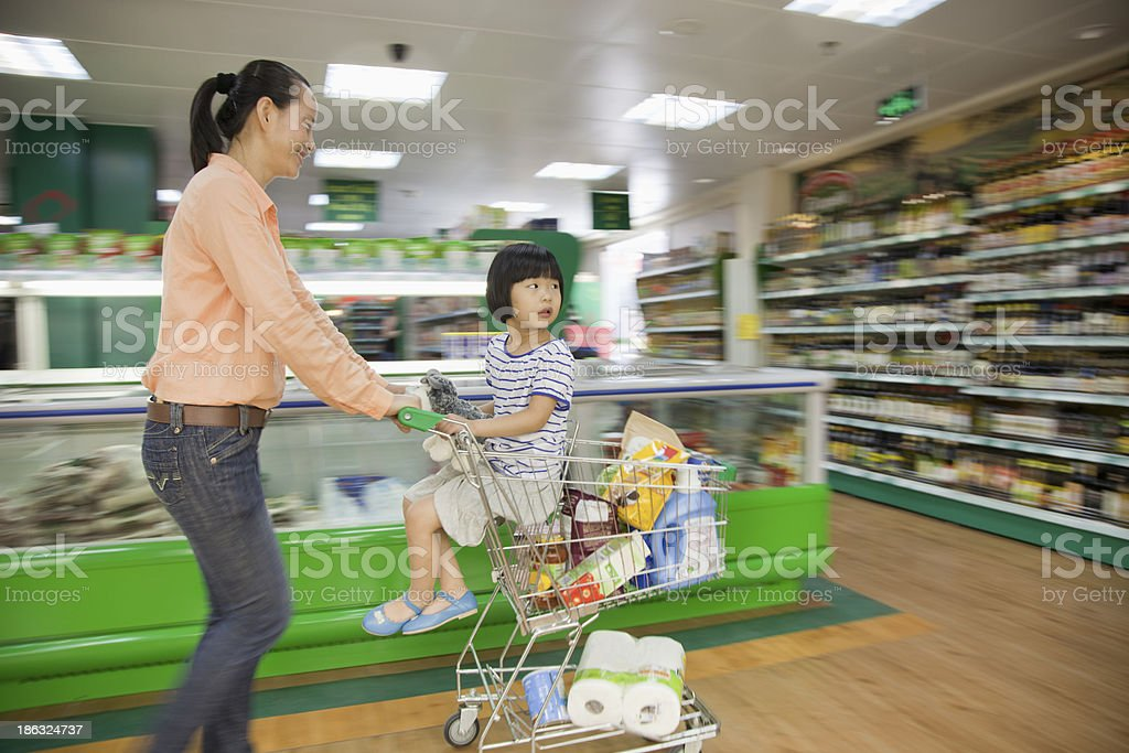 Mother pushing daughter in shopping cart royalty-free stock photo