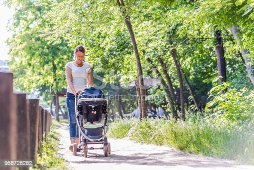Family, child and parenthood concept - Front view of happy mother walking with baby stroller in park during bright summer day. Photo of Young Caucasian mother pushing pram in park on sunny day.   Full length of Beautiful young Female pushing baby carriage in nature.