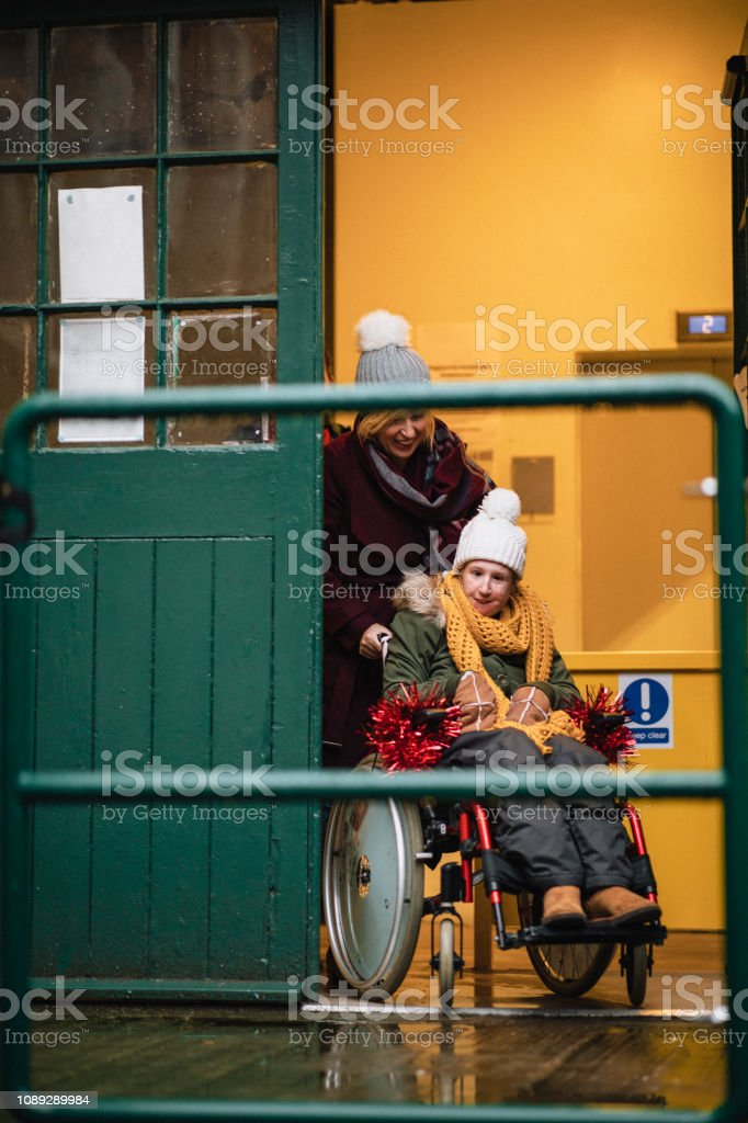 Mother Pushing Daughter in Wheelchair stock photo