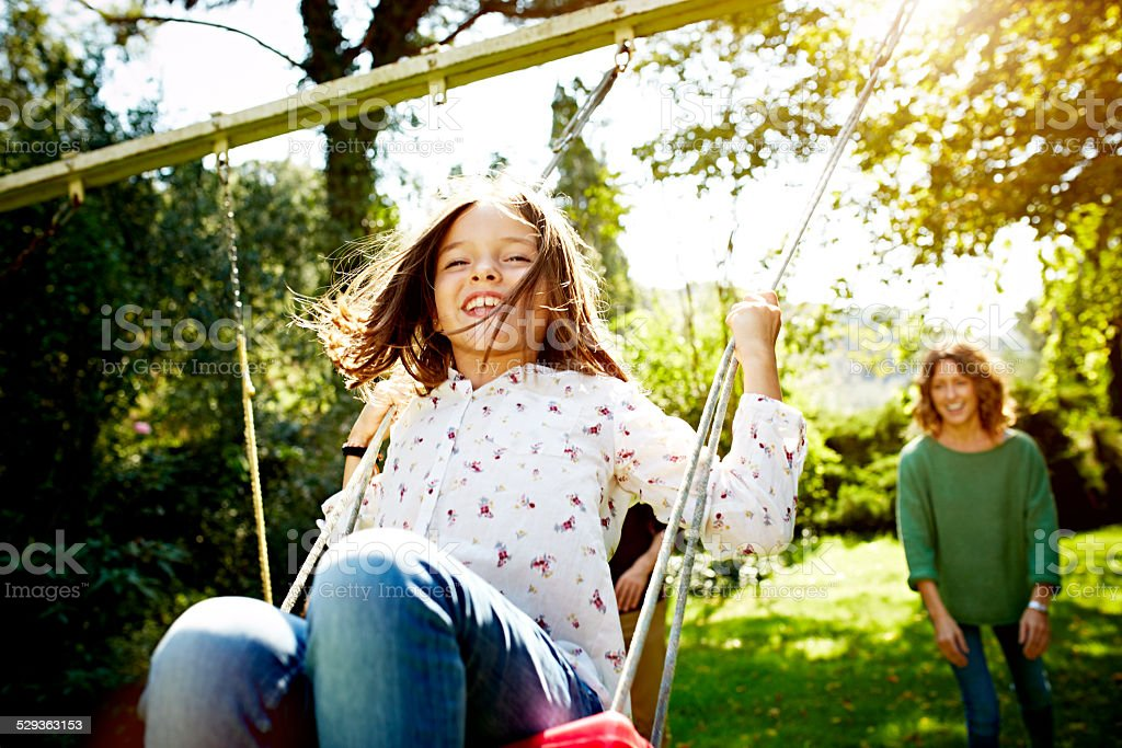 Mother pushing daughter on swing in park - foto stock