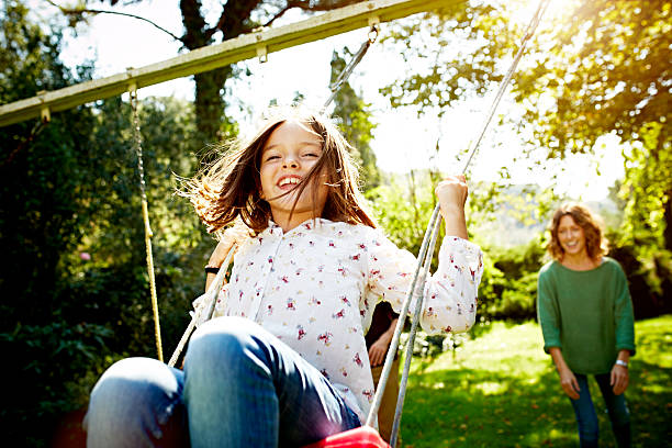 Mother pushing daughter on swing in park stock photo